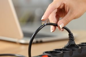 Hand holding a dangerous damaged electrical cord